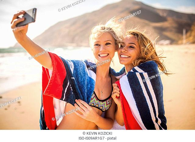 Girlfriends taking selfie on beach, Malibu, California, USA