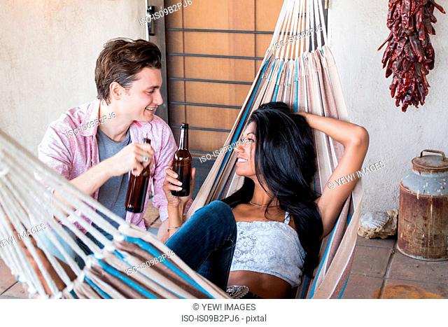 Young couple relaxing on veranda, holding beer bottles, young woman in hammock
