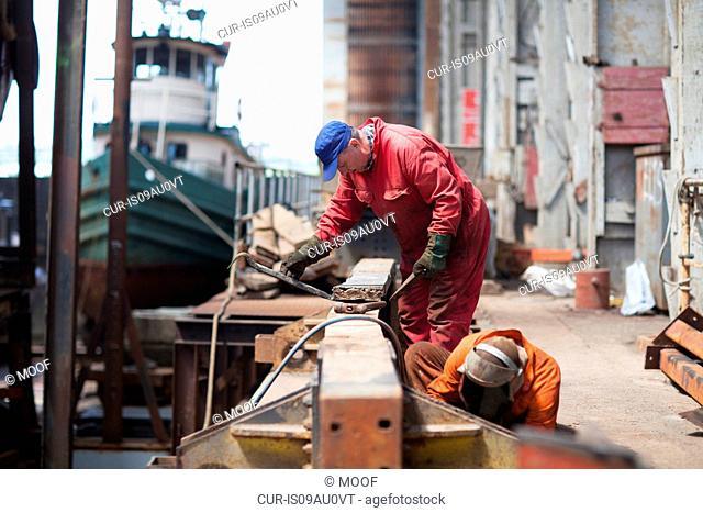 Workers doing maintenance in shipyard workshop