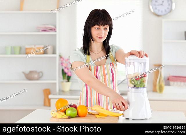 Lovely brunette woman using a mixer while standing