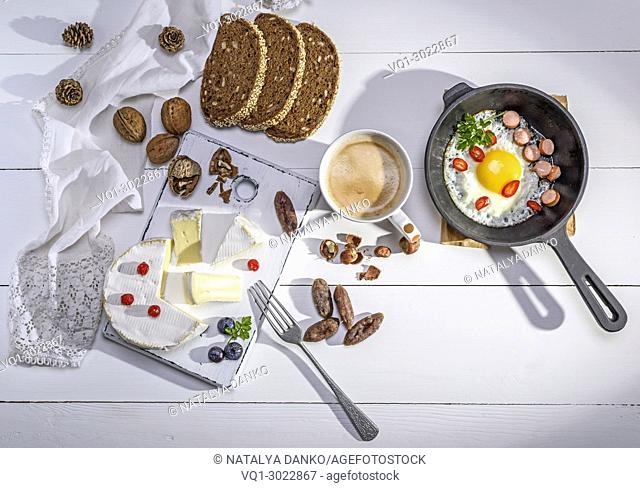 Camembert cheese, a cup of coffee and a black cast-iron frying pan with a fried egg on a white wooden table, top view