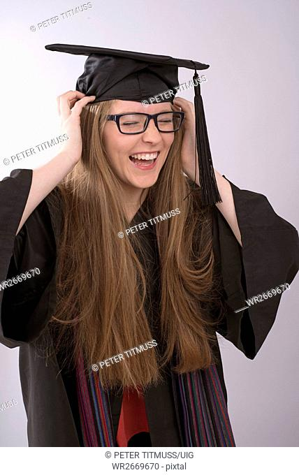 Portrait of a laughing university student adjusting her graduation cap