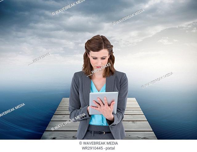 woman on tablet on boardwalk by sea