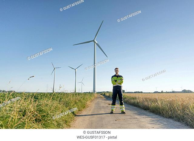 Engineer standing on field path at a wind farm
