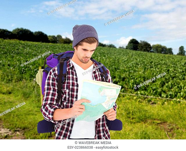 Composite image of man with luggage looking in map
