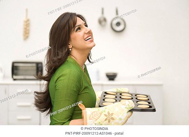 Woman holding a tray of baked cookies and day dreaming