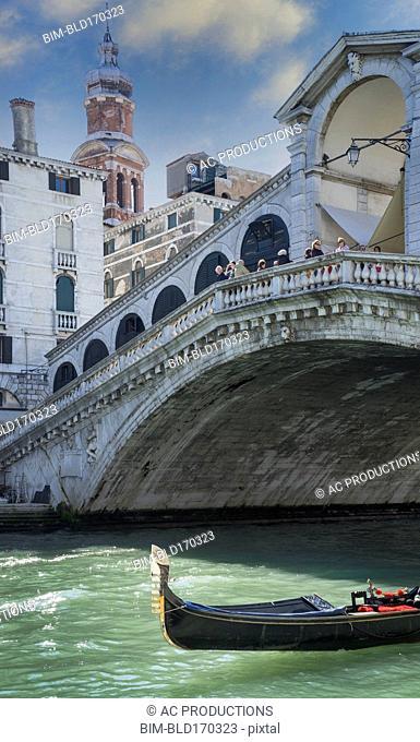 Empty gondola sailing on Venice canal, Veneto, Italy