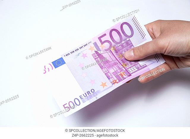 Holding a 500 Euro note in hand