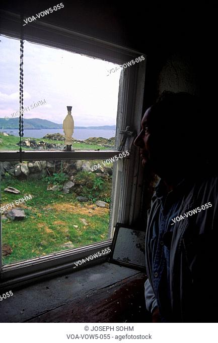 Man looks at View from inside a cottage looking out the window, Cork, Ireland