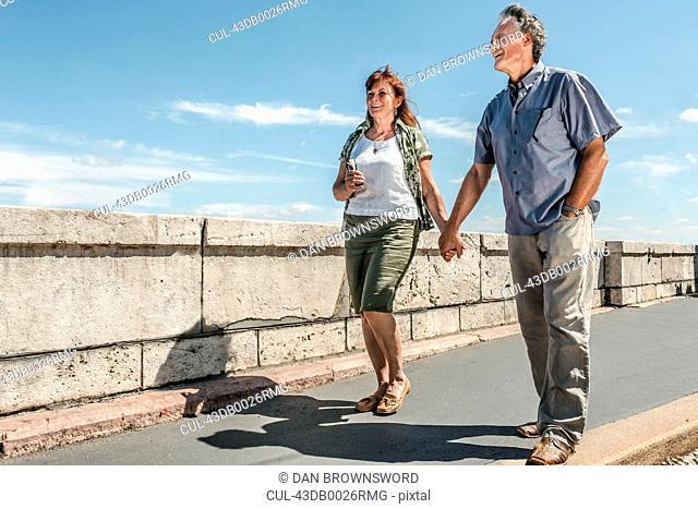 Older couple holding hands on bridge