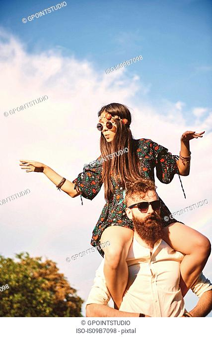 Young boho woman dancing on boyfriend's shoulders at festival