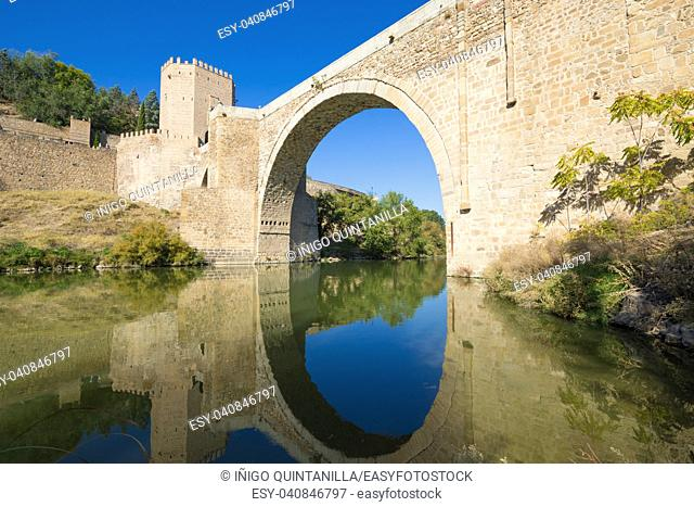 horizontal shot of arch of Alcantara bridge, landmark and monument from ancient Roman age, reflected on water of river Tagus, Tajo in Spanish, in Toledo city