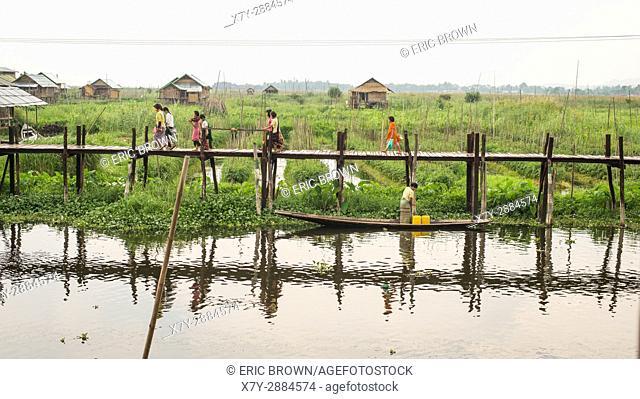 People walking along a dock in Inle Lake, Myanmar