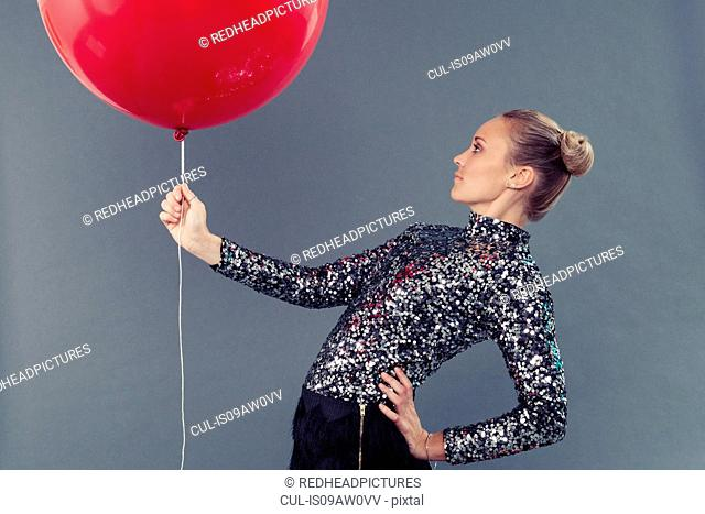 Young woman holding red balloon, grey background