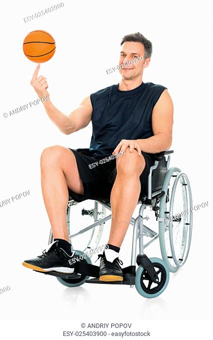 Disabled Basketball Player On Wheelchair Spinning Ball On His Finger Over White Background