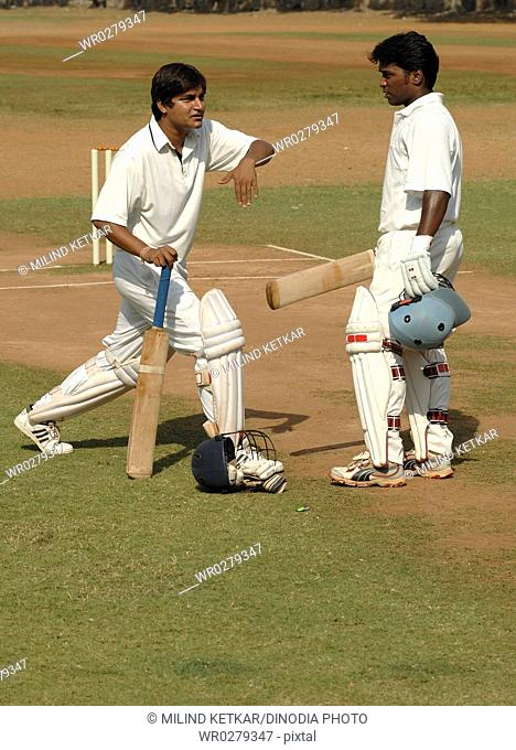 Opening batsmen talking and discussing about strategy plans on pitch in cricket match MR705I, 705L