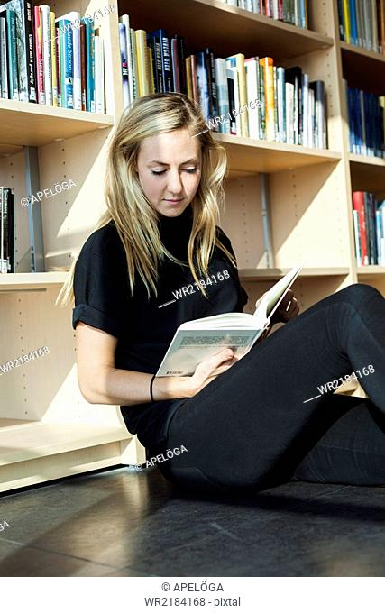 Female student reading book white sitting in college library