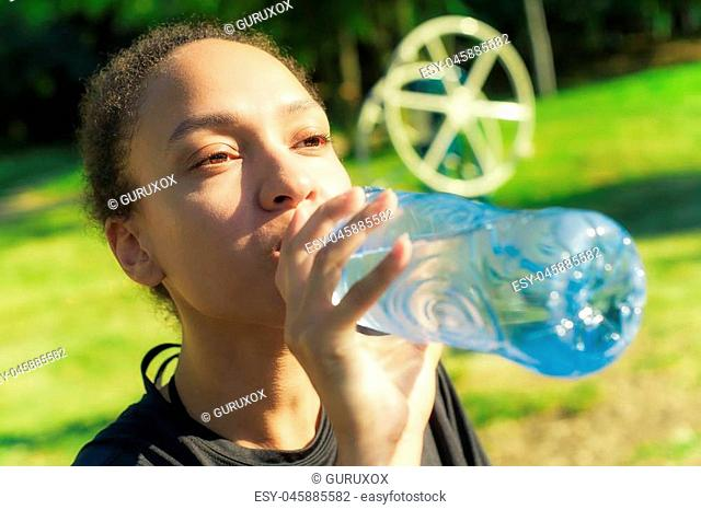 Woman drinking water from bottle after fitness sport exercise