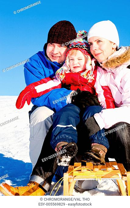 winter activities A happy family sledding downhill