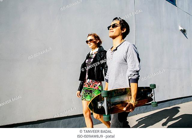 Young couple walking together outdoors, man carrying skateboard