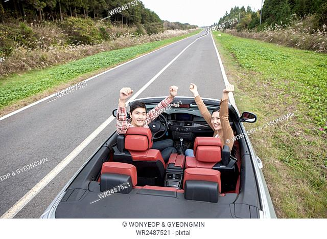 Young smiling couple in a car raising their arms