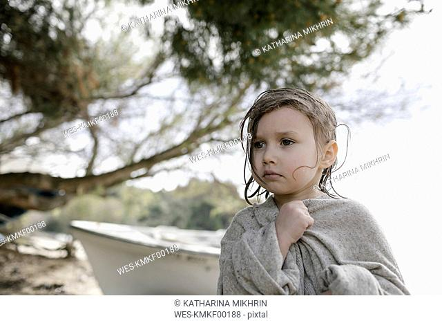 Portrait of sad little girl wrapped in oversized cardigan standing on the beach