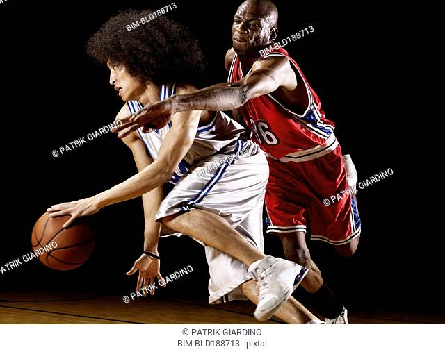 Basketball player trying to take basketball from opponent