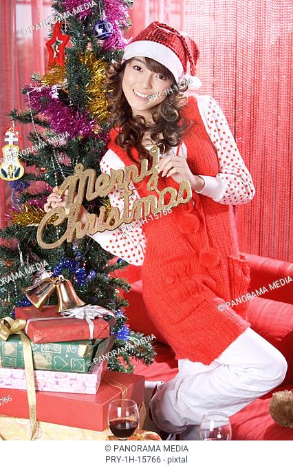 Portrait of a young woman standing by Christmas tree