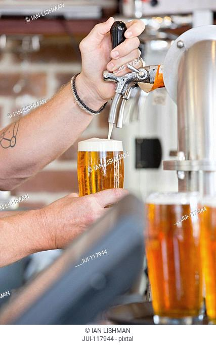 Close Up Of Bartender Pouring Pint Of Beer Behind Counter