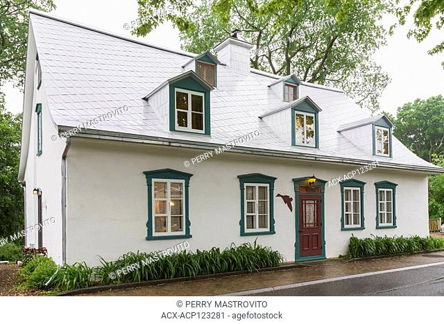 Illuminated old circa 1805 white roughcast with green and burgundy trim Canadiana cottage style home facade in late spring, Quebec, Canada