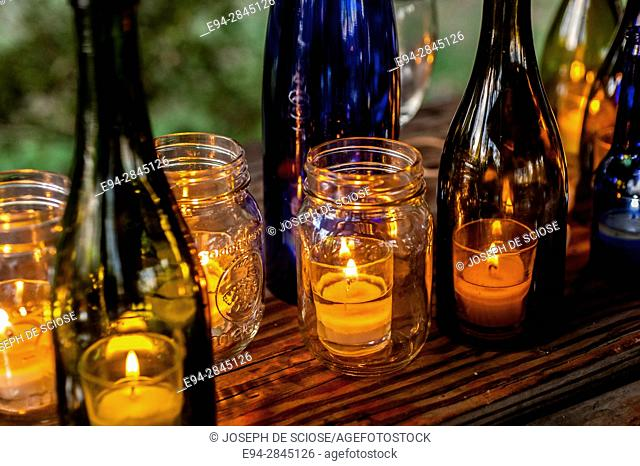 A row of colored bottles and jars holding lighted candles on a table outdoors