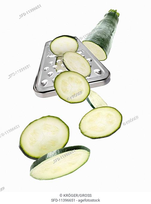 A grater with a courgette and courgette slices
