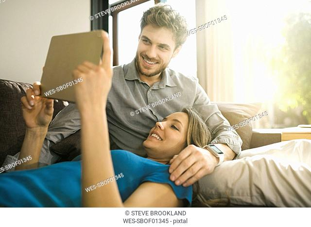 Smiling couple looking at tablet and relaxing on sofa at home