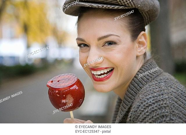 Portrait of young happy woman eating candy apple