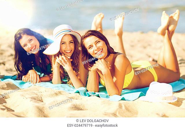 summer holidays and vacation - girls in bikinis sunbathing on the beach