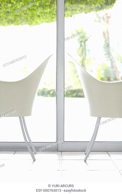 Image of two white chairs placed back to back by a glass window