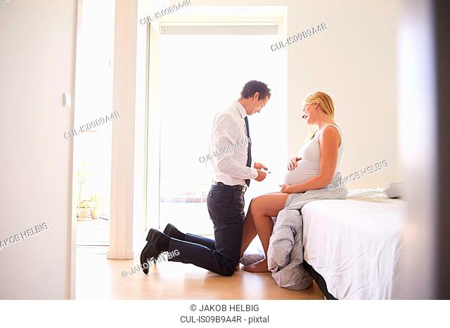 Man looking at ultrasound pictures with pregnant girlfriend in bedroom