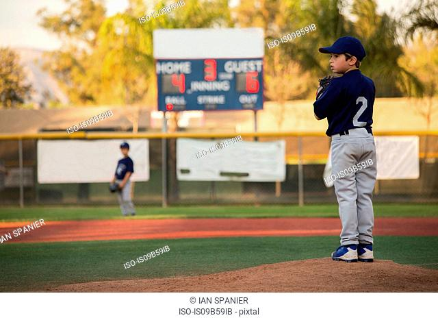 Boy baseball pitcher preparing to throw on baseball field