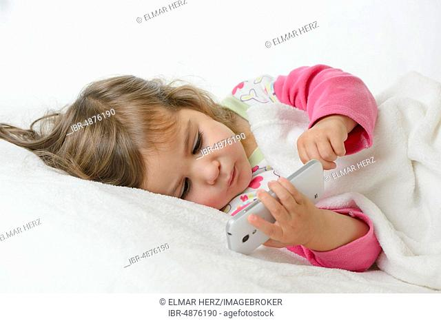 Girl, 2 years, portrait, lying with mobile phone, Germany
