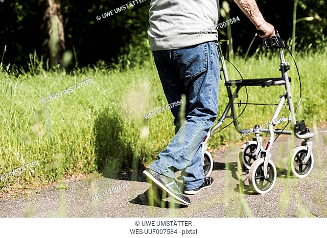 Back view of senior man strolling with wheeled walker in nature