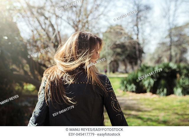 Young blonde woman from behind wearing a leather jacket in the park moving her hair