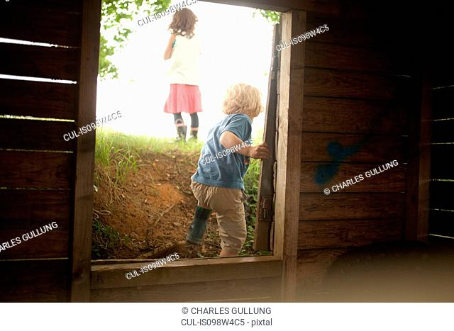 Boy and girl leaving through wooden window frame