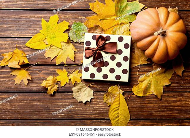Present gift and pumpkin with autumn leafs on wooden table