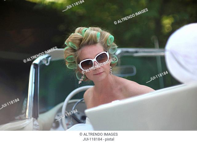 Bride In Open Top Car Wearing Hair Curlers On Wedding Day