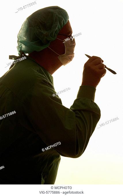 Germany, HAMBURG, 29.12.2006, Siluette von einem Chirurgen mit einem Skalpell in der Hand - Hamburg, Germany, 29/12/2006