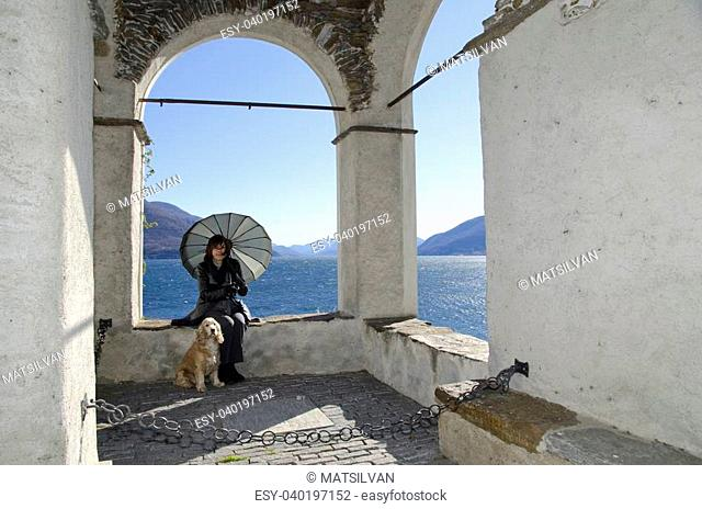 Woman with her dog sitting under a arch with a lake and mountain in background