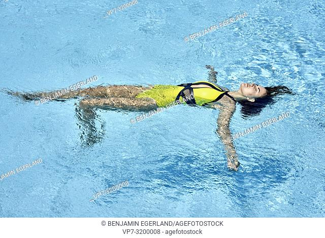 woman floating, in pool, relaxation, recreation, summer, holiday