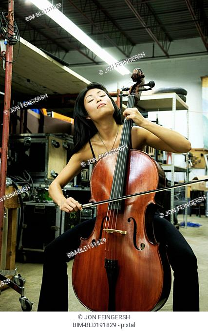 Asian woman playing cello in warehouse