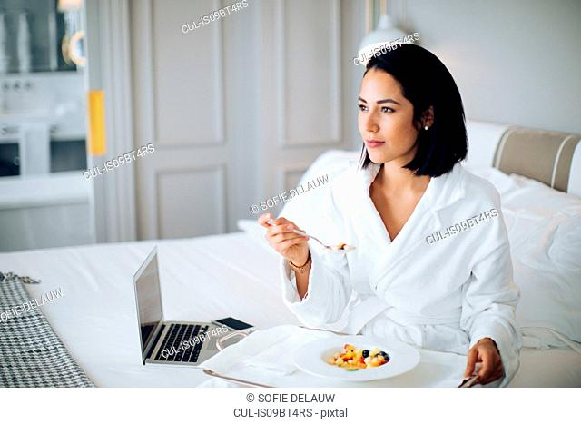 Woman using laptop and having breakfast in suite