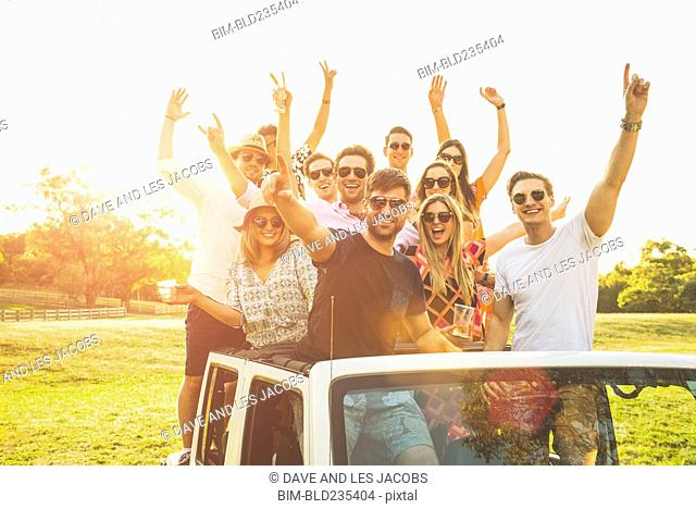 Portrait of friends waving in off-road vehicle
